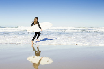 Teenage girl running on the beach with her surfboard