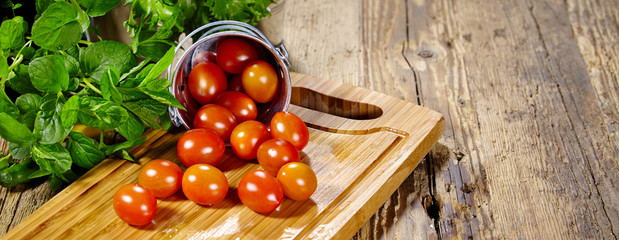 Cherry tomatoes with basil on a wood table