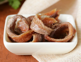Canned marinated anchovies fillets in a white bowl