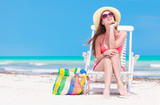 Woman in bikini and straw hat with beach bag sitting on chair on