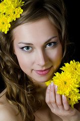 The girl with beautiful hair with yellow chrysanthemum