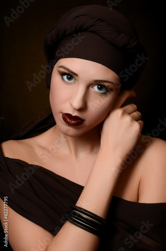 The beautiful woman in a turban with a creative make-up
