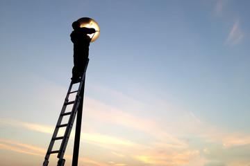 electrician fixing street light bulbs and climbing on a ladder