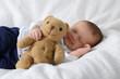 Newborn mit Teddy lacht