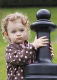 Little toddler playing chess outside