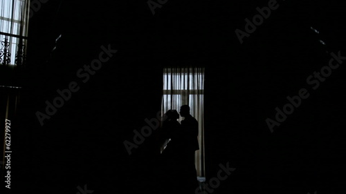 silhouettes of the bride and groom on the background of a window