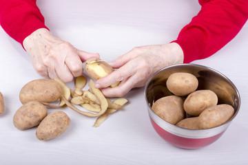 Alte Frau schält viele Kartoffel aus einem Kochtopf