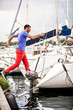 Handsome latin man jumping on yacht from pier