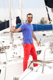 Full length portrait of sexy man standing on white yacht