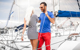 latin man inviting sexy blonde woman on his yacht