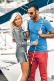 Portrait of handsome latin man and blond woman standing on yacht