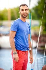 Portrait of stylish latin man sailing on yacht