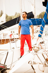 Handsome stylish macho standing on white yacht