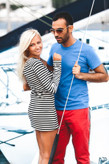 handsome latin man hugging sexy blonde woman on yacht