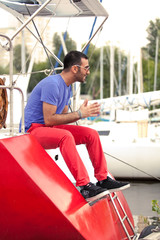 Handsome latin man sitting on deck of red yacht at seaport