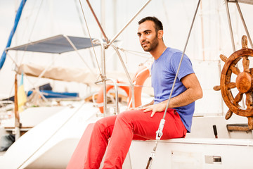 Stylish latin man sitting on yacht deck