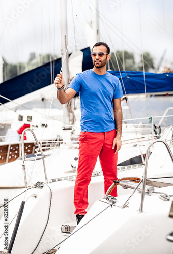 Stylish latin man in sunglasses standing on white yacht