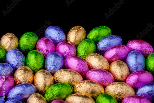 Chocolate Mini eggs wrapped in foil, black background