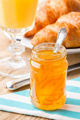Orange jam with juice and croissants.  Shallow depth of field.