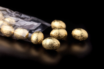 Chocolate mini eggs in a cellophane bag on a black background
