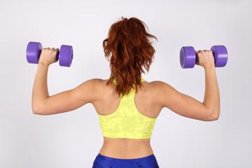 Mujer joven practicando pesas de espalda