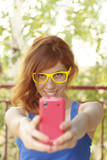 Hipster girl smiling and taking photo with her pink smart phone