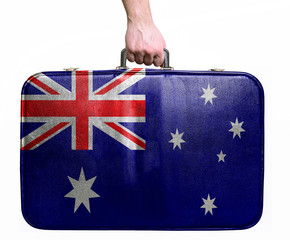 Tourist hand holding vintage leather travel bag with flag of Aus