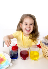 little girl dying traditional eggs in vivid colours celebrating