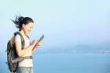 woman hiker seaside use digital tablet