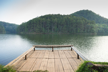 Pier in lake with mountain background.