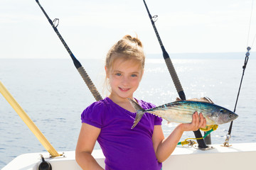 Blond girl fishing bonito Sarda tuna trolling in sea
