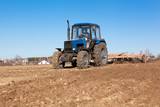 Farmer cultivating soil and preparing field for planting