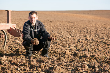 Farmer man in cultivated field holding soil in palms