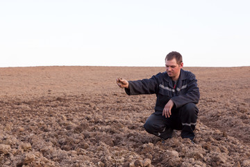 Farmer man in cultivated field looking at soil