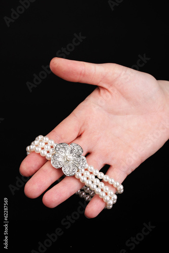 Pearl bracelet in hand isolated on black