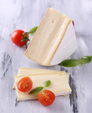 Tasty Camembert cheese with tomato and basil, on wooden table