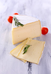 Tasty Camembert cheese with tomato and rosemary, on wooden
