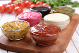 Various sauces on chopping board on table close-up