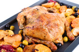 Whole roasted chicken with vegetables on tray, isolated on