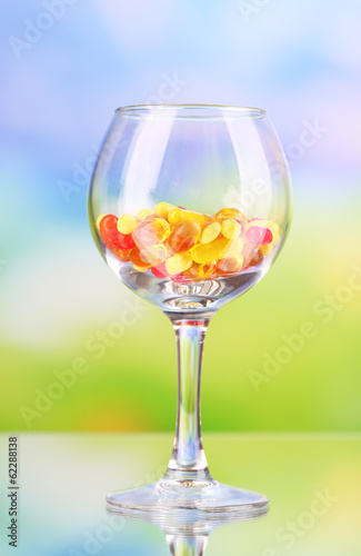 Goblet with pills on natural background