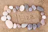 Inscription Ibiza in wet sand close-up background