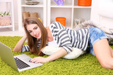 Young woman resting with laptop on floor near sofa, at home