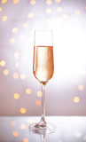 Glass of champagne on shiny background