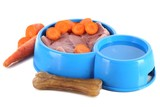 Natural food for pets and water in plastic bowls isolated