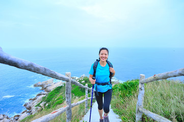 woman hiker on seaside mountain peak
