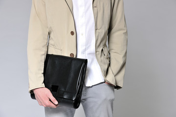Young man holding a briefcase with hand in pocket