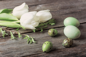 green easter eggs  and tulips on wooden background