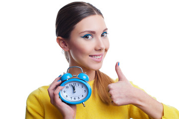 Young beautiful woman holding light blue clock