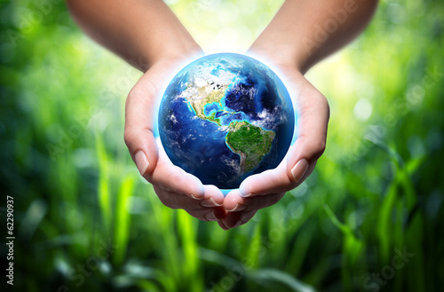 Leinwanddruck Bild earth in hands - grass background - environment concept