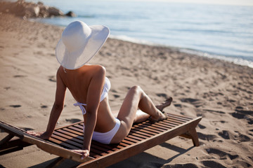 Young woman sunbathes sitting on sunbed.